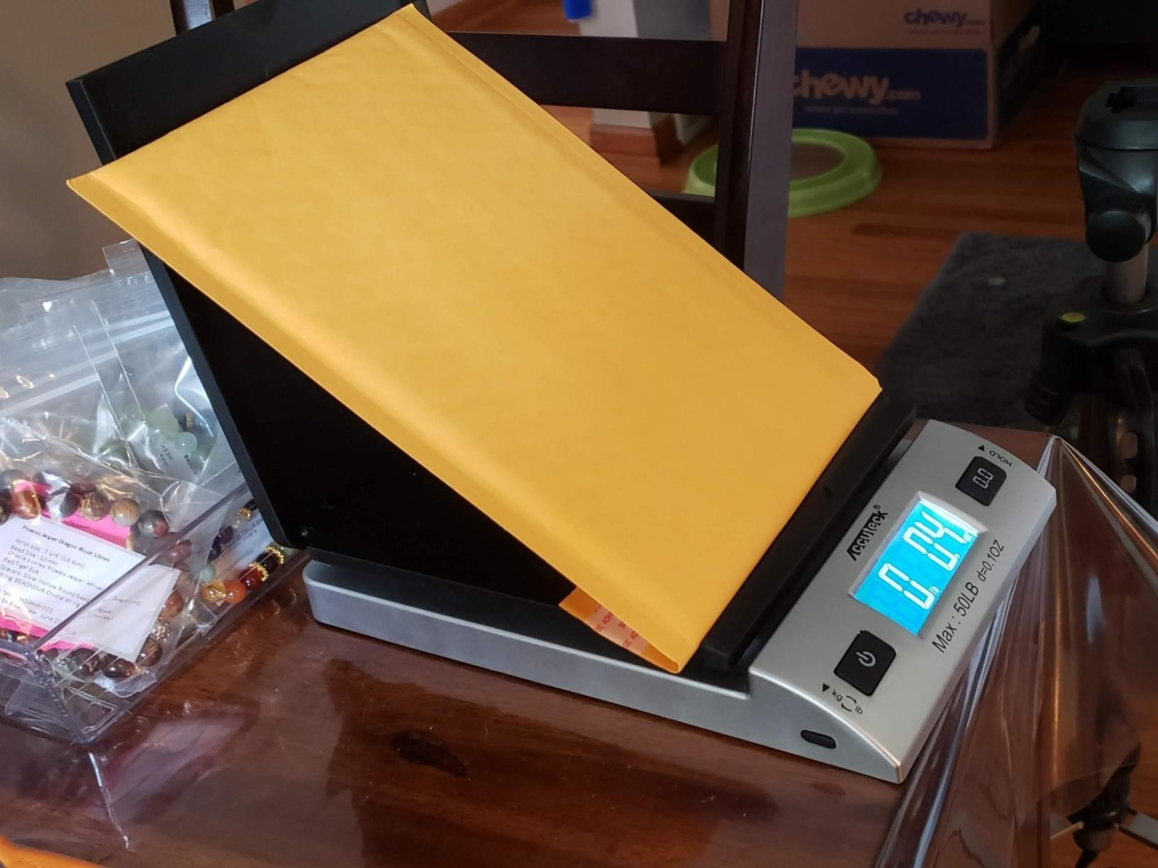 A small silver and black home digital scale with a manila envelope being weighed