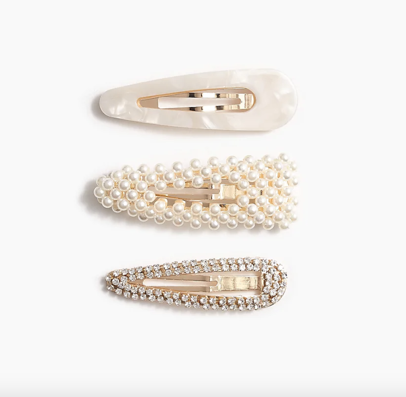 Three different-styled pearl clips — the top one plain acrylic, the middle one pearl-studded, and the third one covered in rhinestones — against a plain background against a plain background