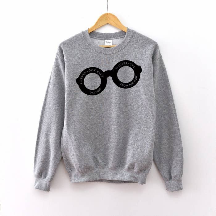 "a grey pullover with black glasses on it that says ""i never look back darling it distracts from the now"" inside them"