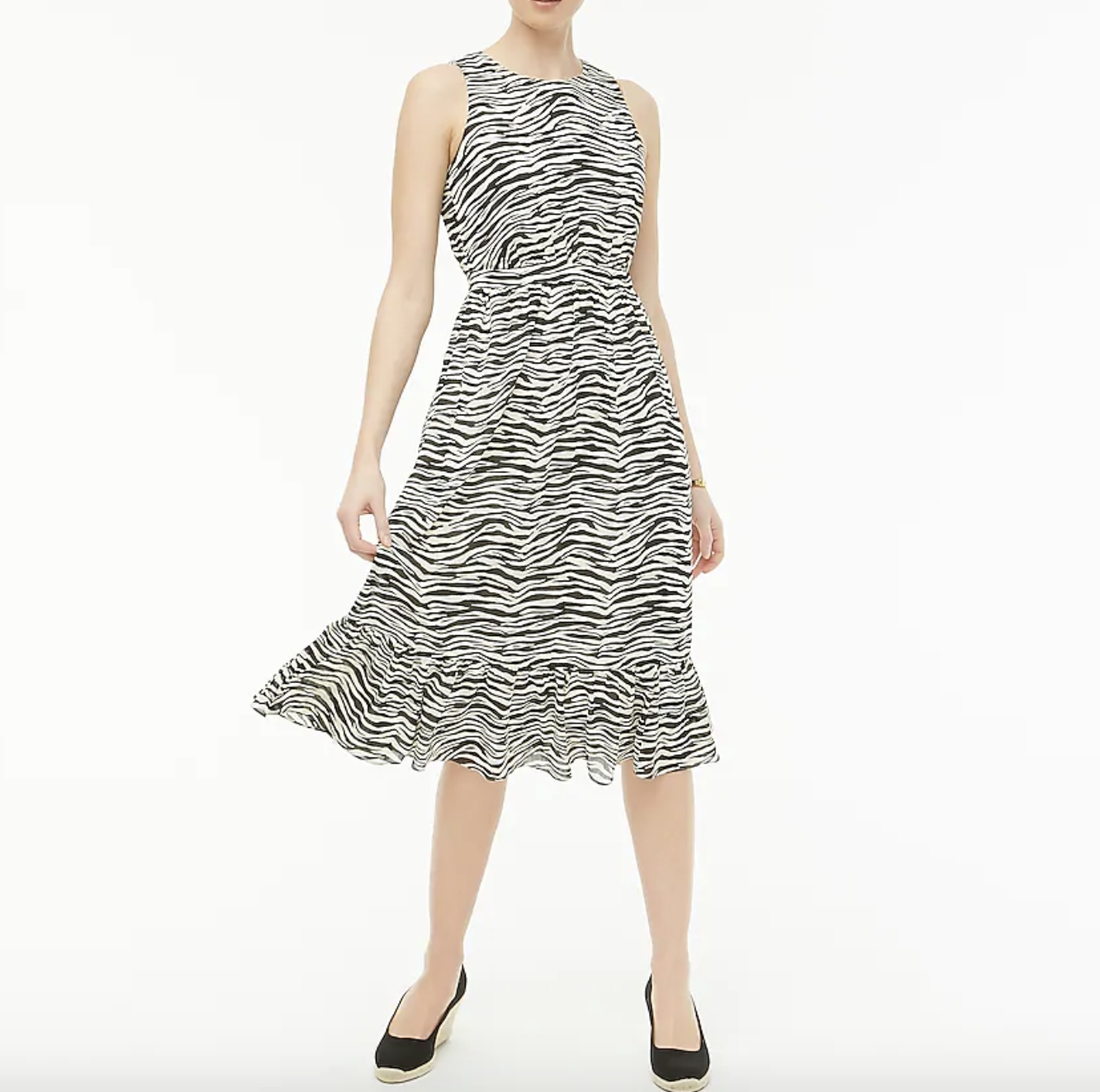 A model wearing a black-and-white tiger print–like midi dress with black canvas wedges