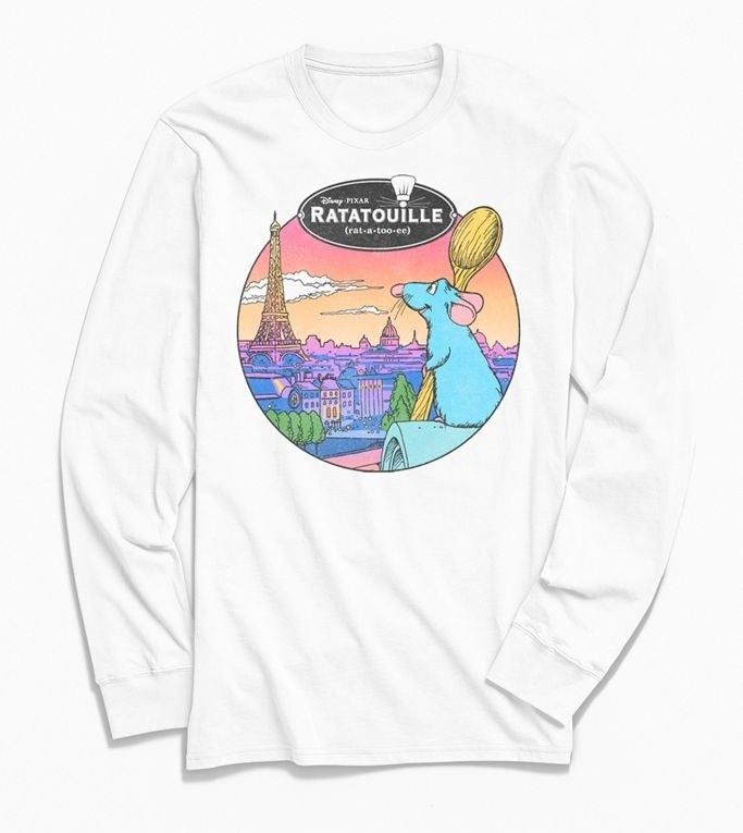 a white long sleeve shirt with remy from ratatouille on it holding a spoon and looking out at the city