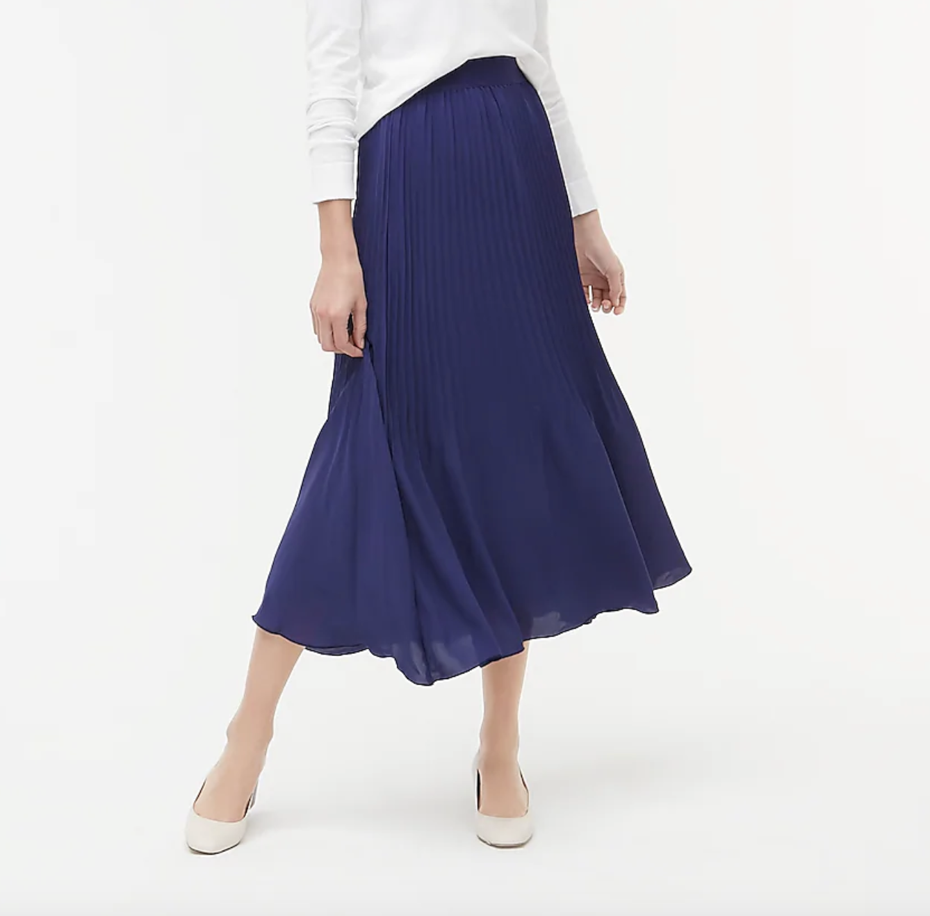 A model wearing the skirt in blue with a white long-sleeve top tucked into it and nude shoes