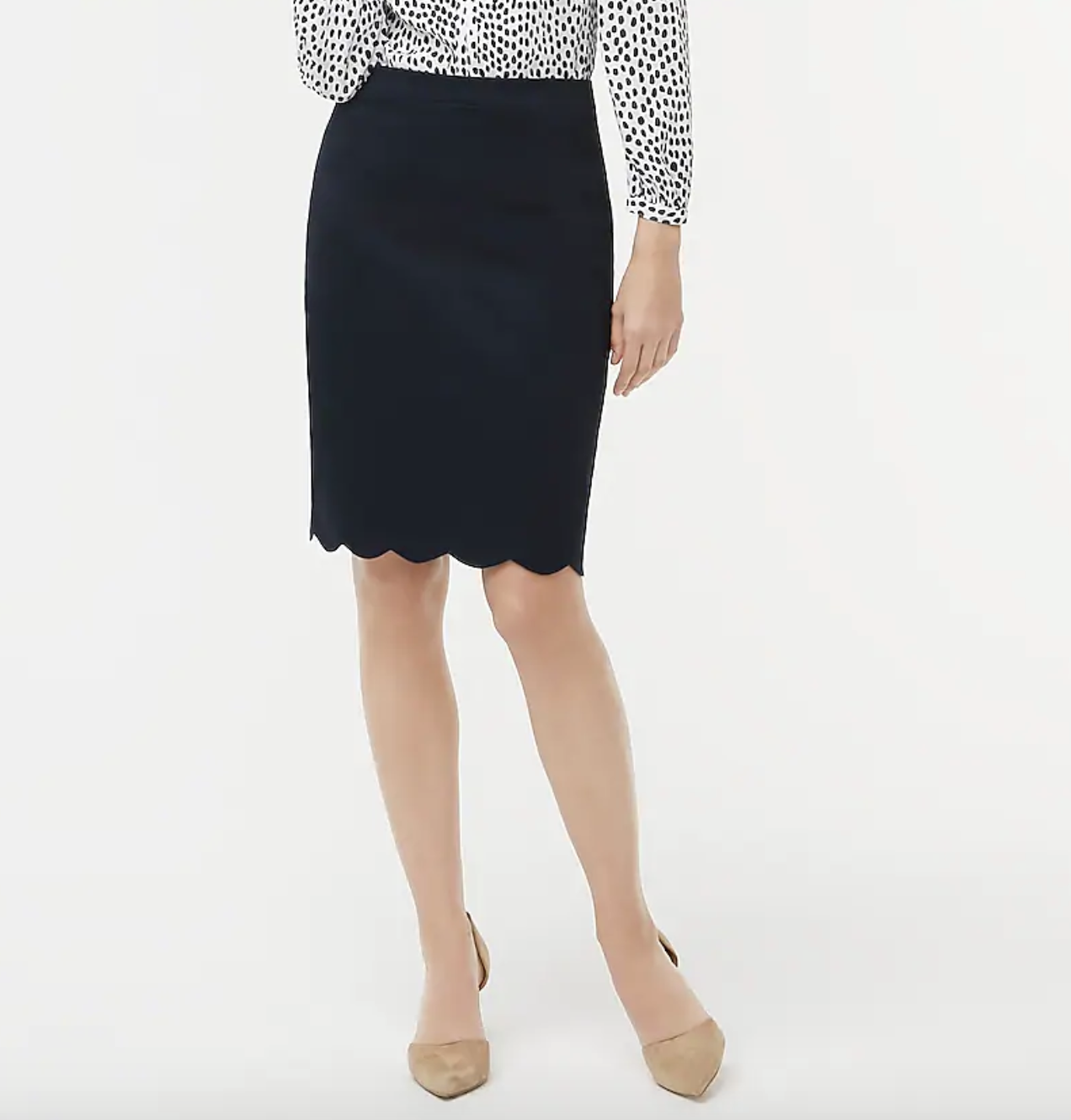 A model wearing the skirt with a black and white blouse tucked into it and nude flats