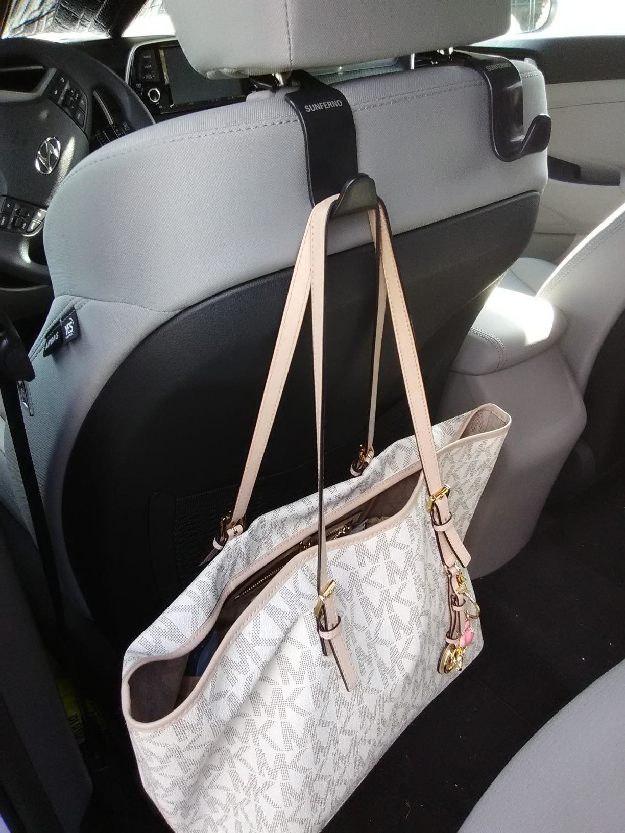 A Michael Kors handbag secured to a car headrest hook hanging from the back of the driver's seat