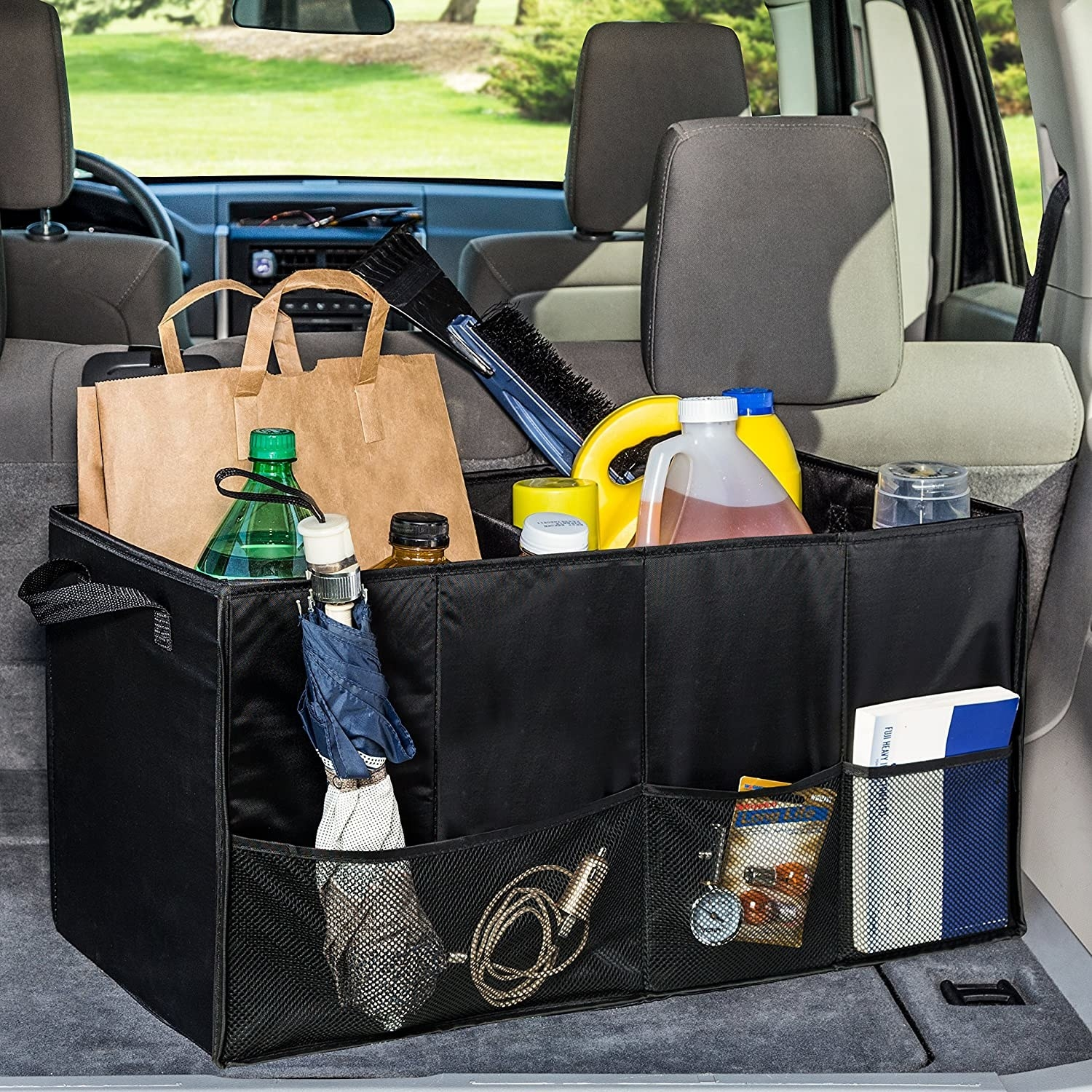A black trunk organizer inside a car trunk filled with car accessories, groceries, an umbrella and more in its mesh side pockets