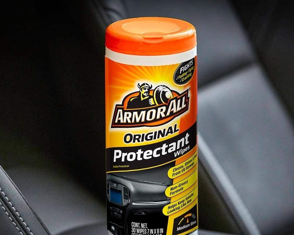 An orange, yellow, and white container of Armor All wipes sitting atop the black leather interior of an automobile