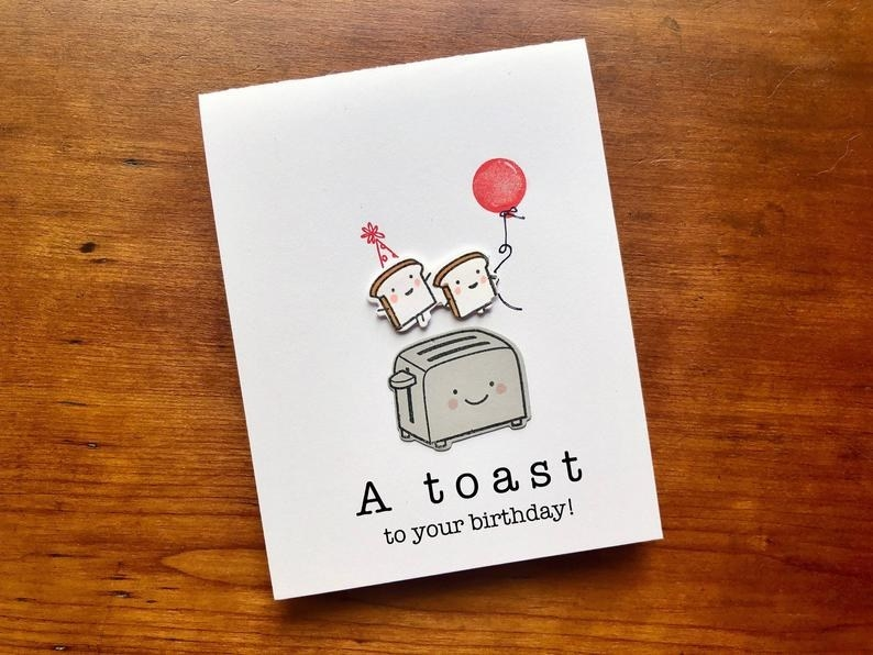 """A card that reads """"A toast to your birthday"""" with a pop up toaster and two pieces of toast with party gear holding hands"""