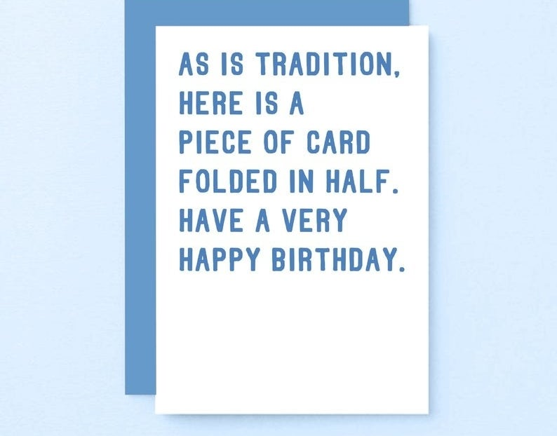 """A white card with blue text that reads """"As is tradition, here is a piece of card folded in half. Have a very happy birthday"""""""