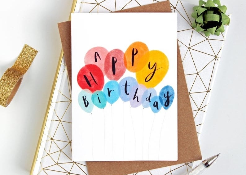 """A card that reads """"Happy birthday"""" on colorful watercolor balloons"""