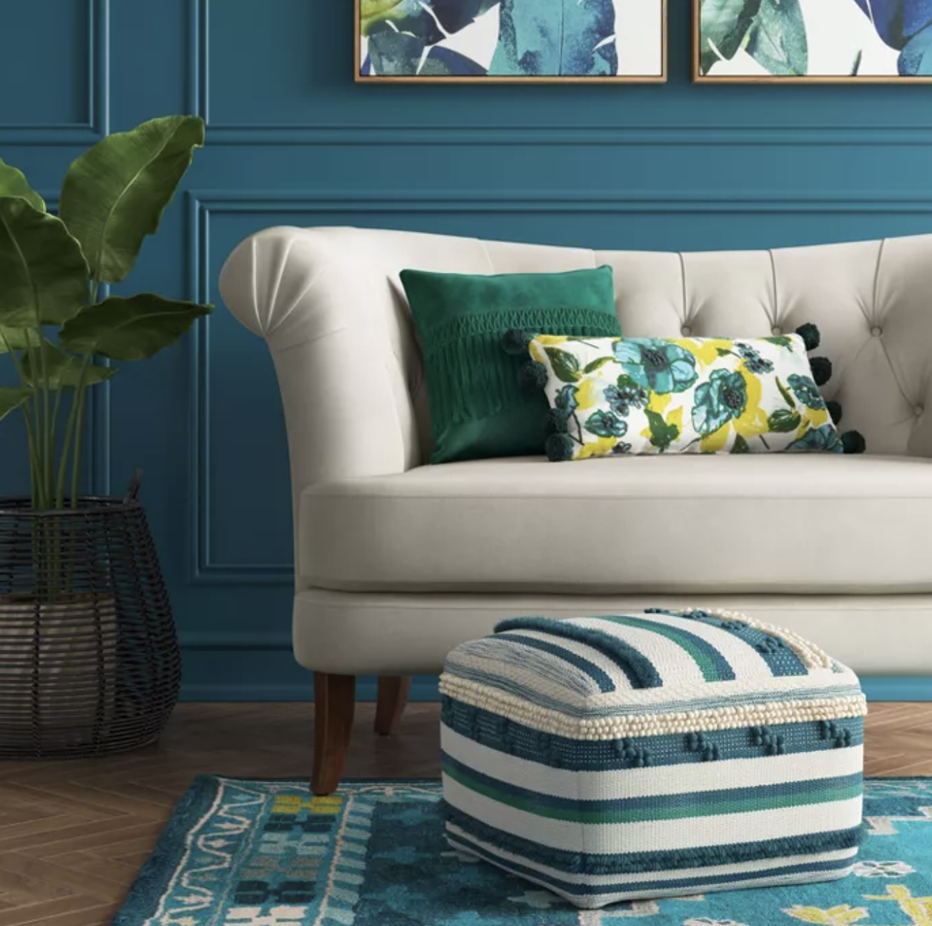 Teal, blue, and white striped pouf next to a white couch with green and floral pillows