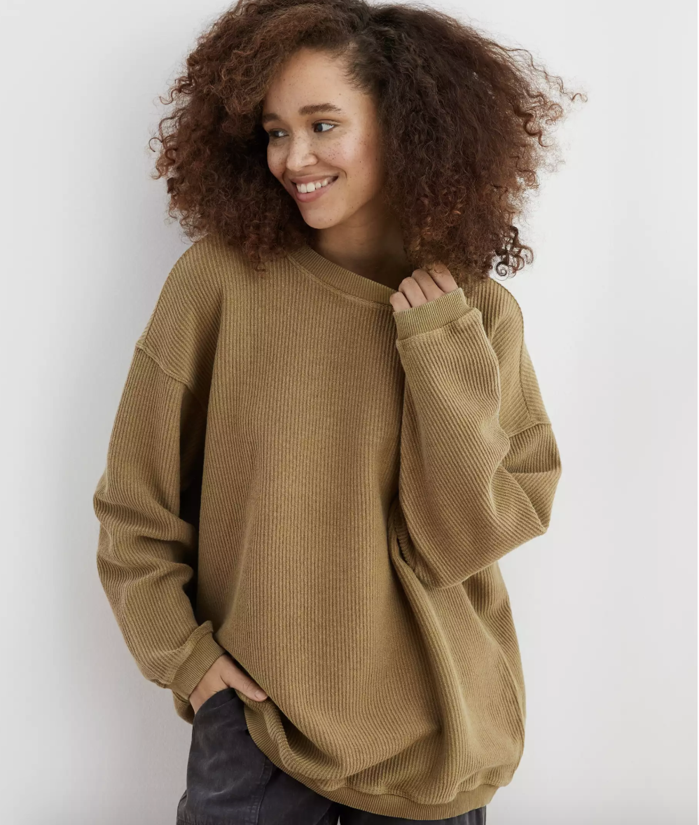 A person wearing a green oversized ribbed sweater that falls below the hip