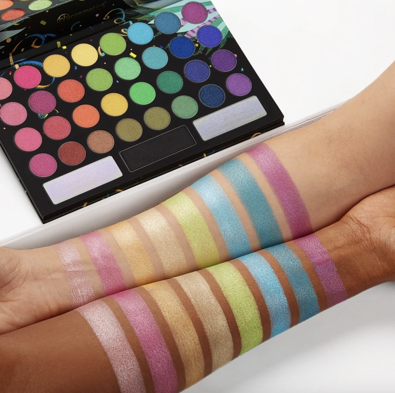 A bright and bold eyeshadow palette with swatches of eight different colors on both a lighter skinned arm and a darker skinned arm