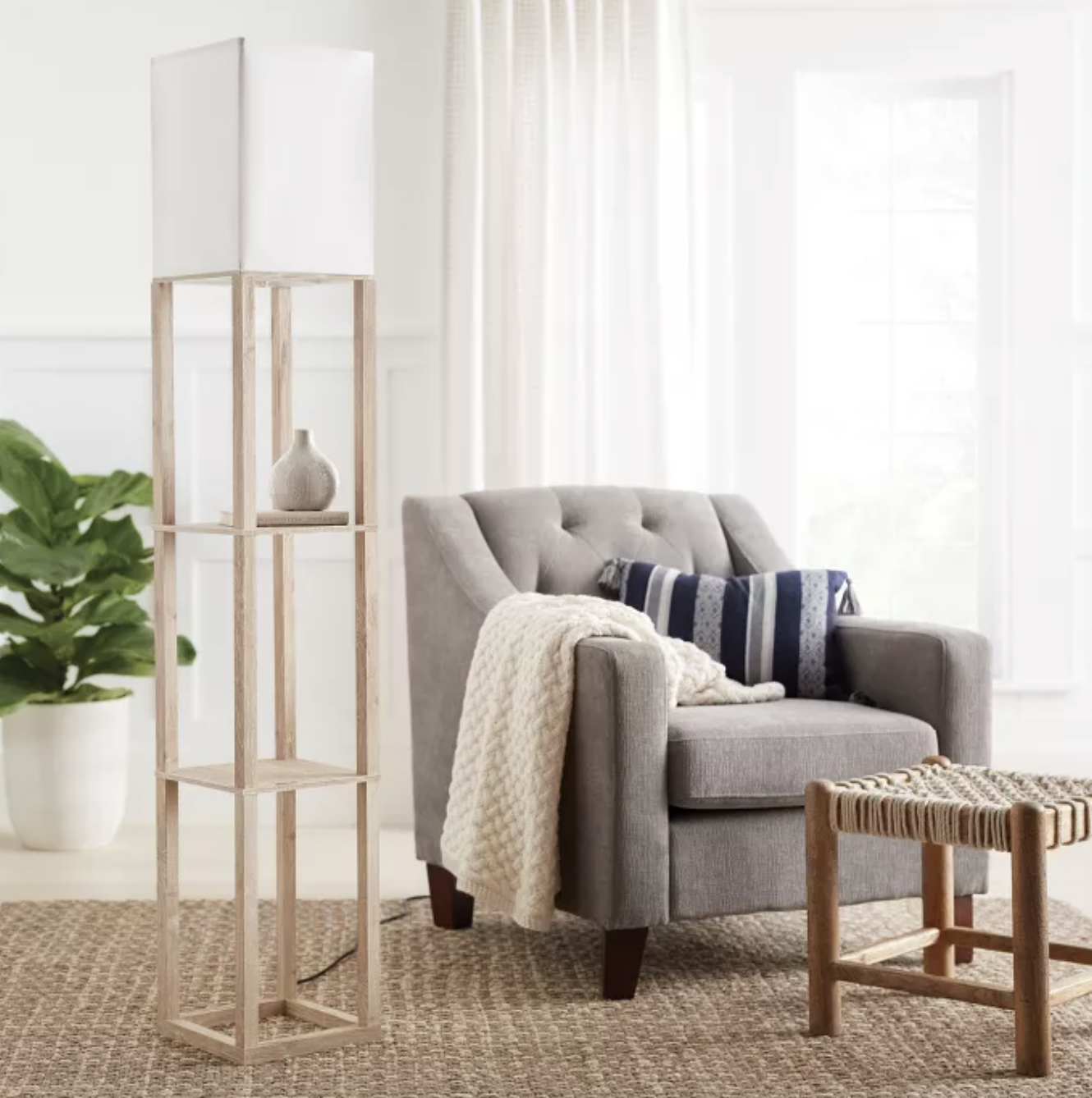 Wooden rectangular lamp with two mini shelves next to gray armchair