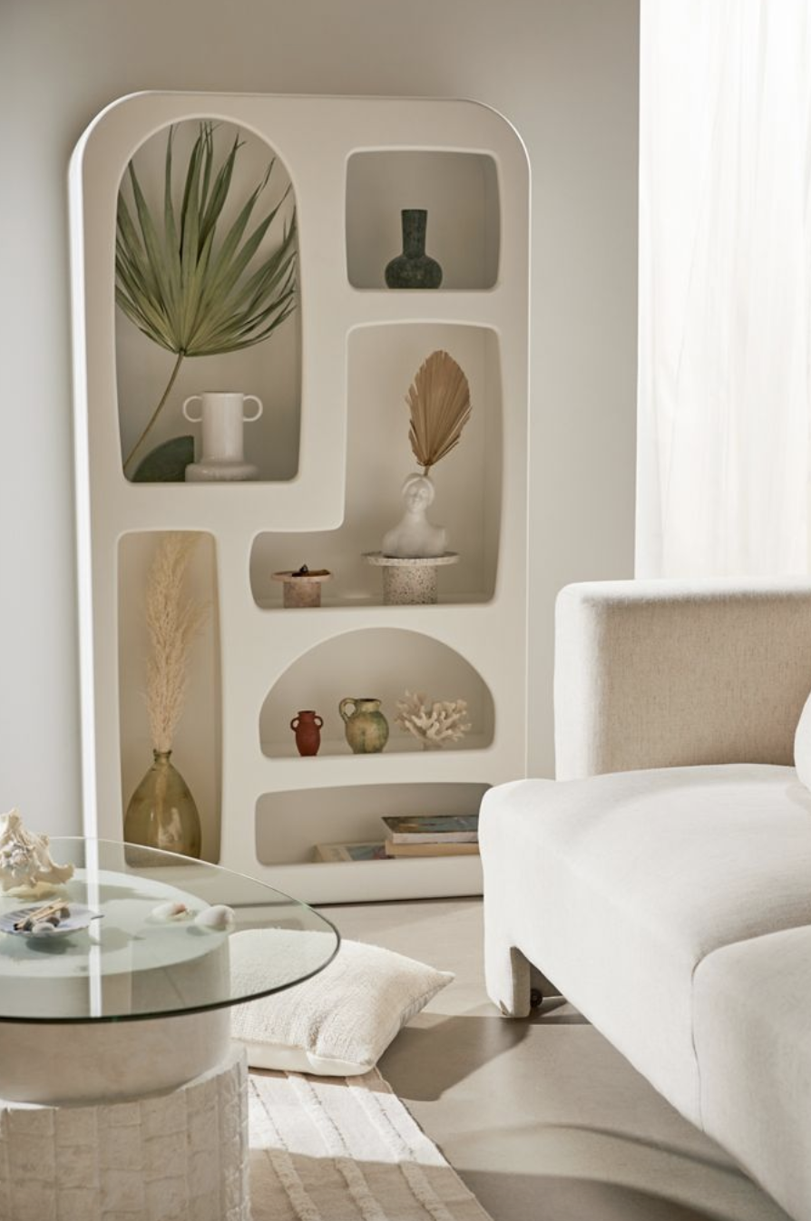 Abstract white bookshelf filled with circular shelves next to a white couch