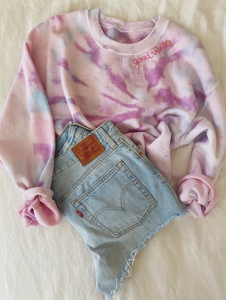 """A tie-dye pullover sweater in pink with accents of purple and blue and the words """"good vibes"""" and a little sun embroidered under the collar on the right side, posed with a pair of denim shorts"""