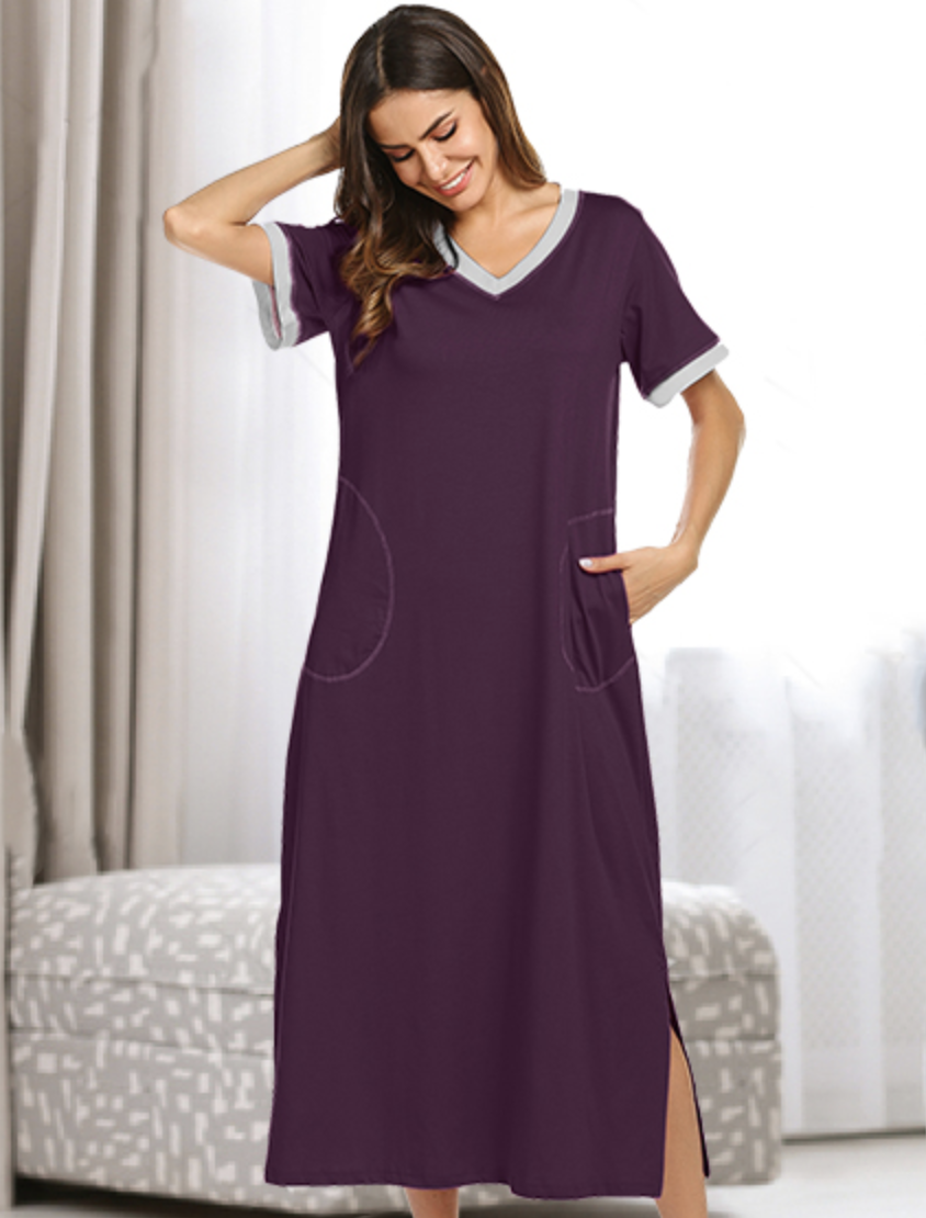 A person wearing a purple ankle-length V-neck nightgown with a white-trimmed collar and sleeves and pockets at the hips