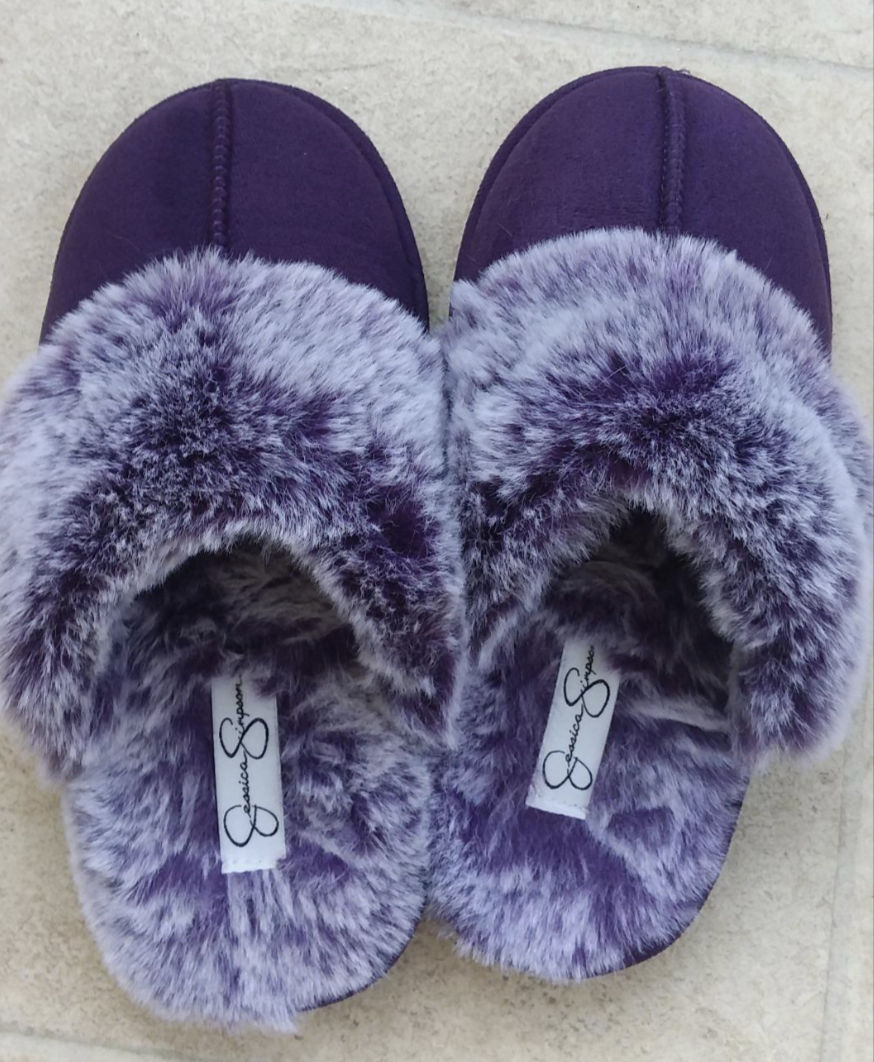 A pair of purple faux fur-lined slip-on slippers that cover your toes