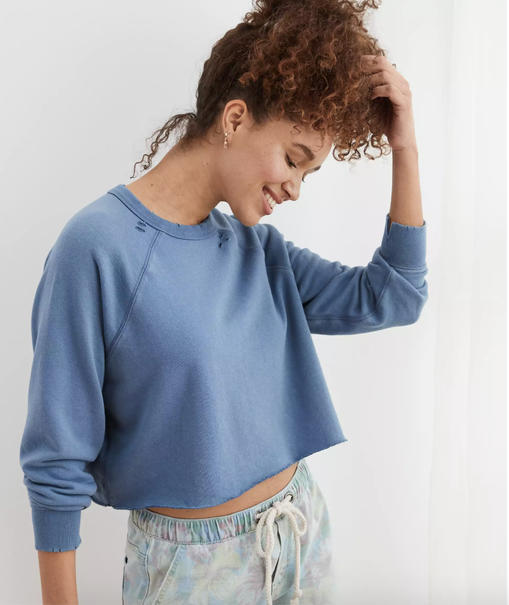 A person wearing a cropped blue pullover sweater that's slightly distressed at the collar and the sleeves