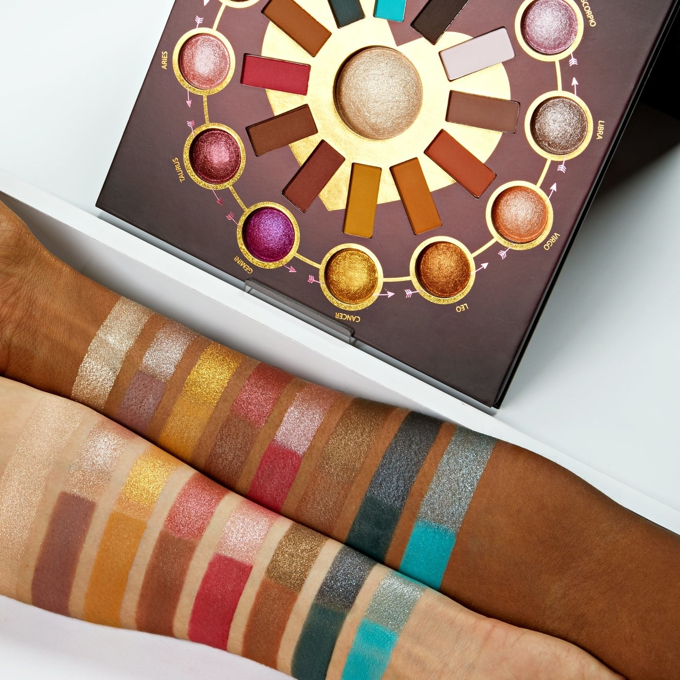 Two arms covered in eyeshadow swatches display the colors. The palette pans are arranged in a circle with the highlighter in the middle
