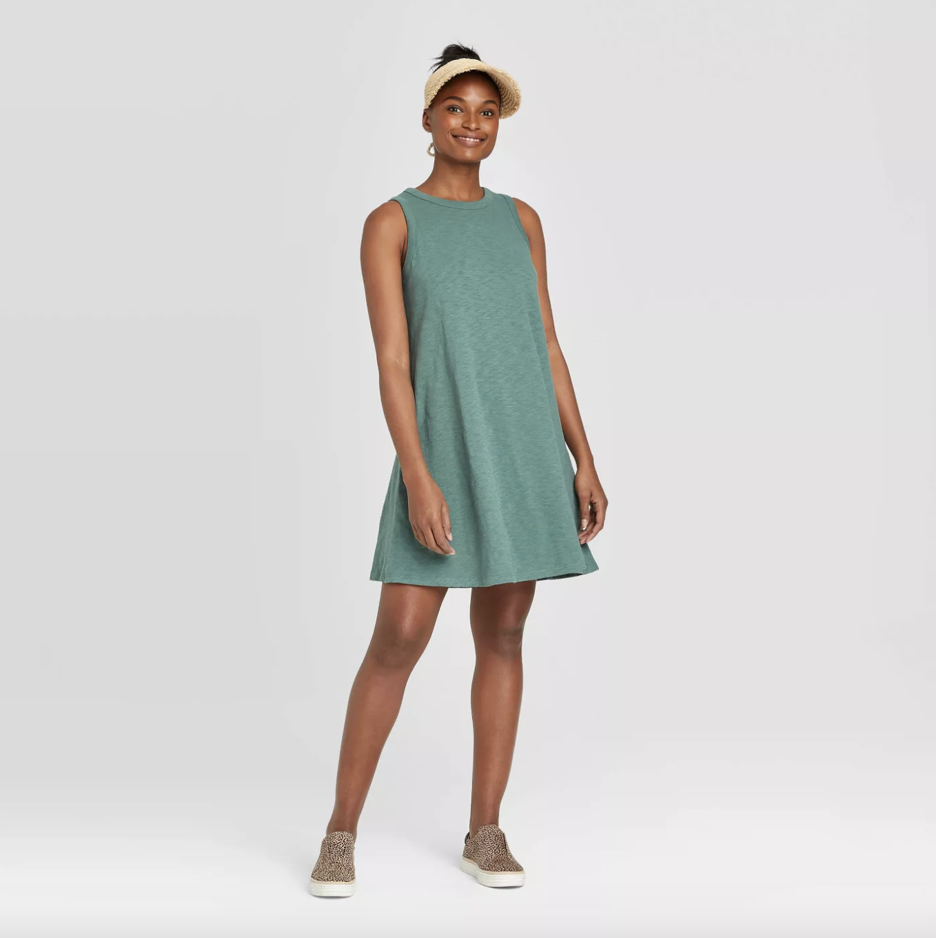 A person wearing a green-colored swing hem dress with tank sleeves that falls just above the knee