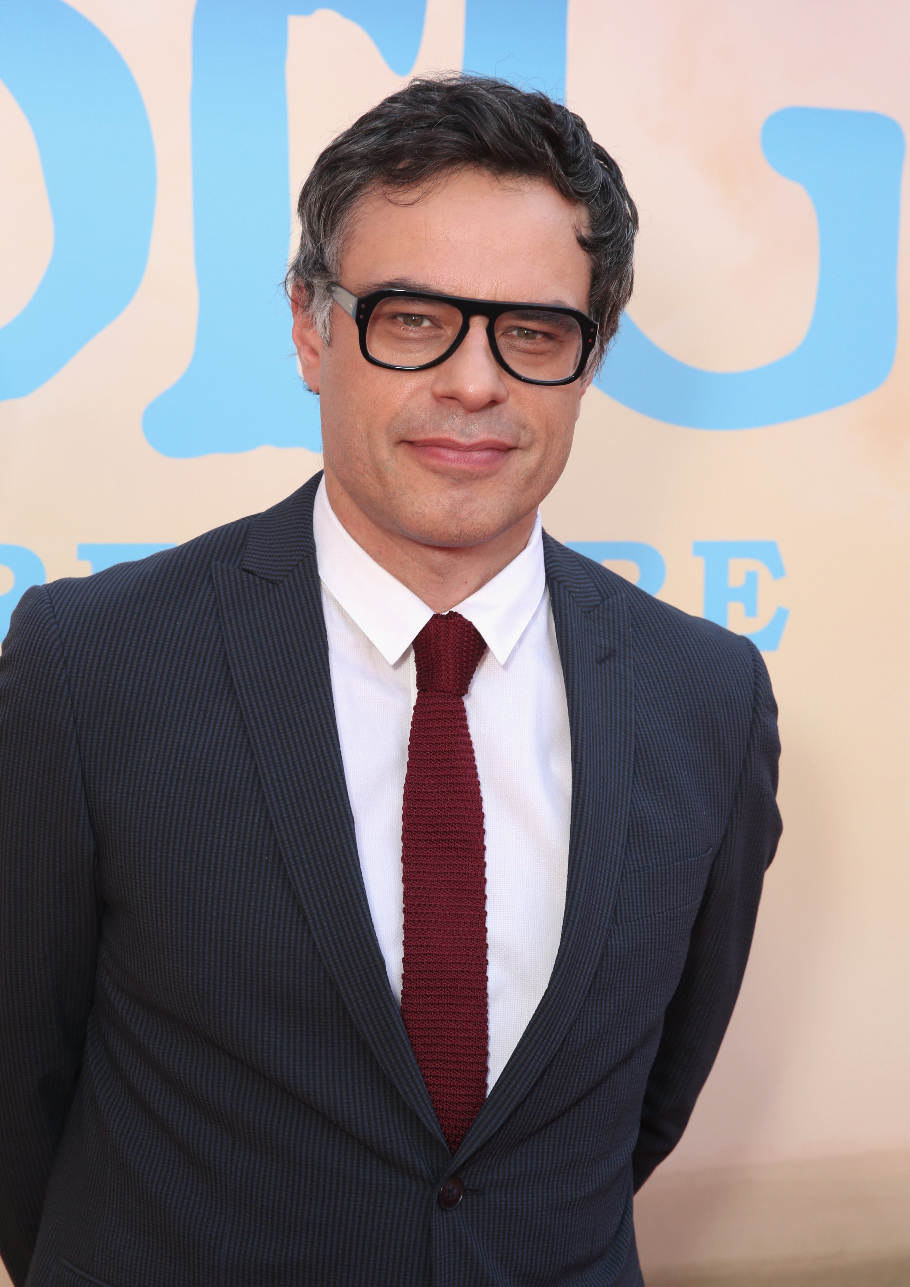 Jemaine Clement smiles with his hands clasped behind his back as he wears a black suit and red tie