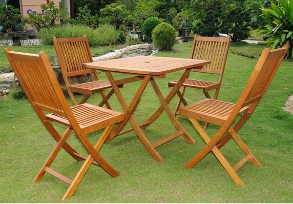 yard with a dining set of four wood folding chairs and a square-shaped folding table. Chairs do not have arms or cushions