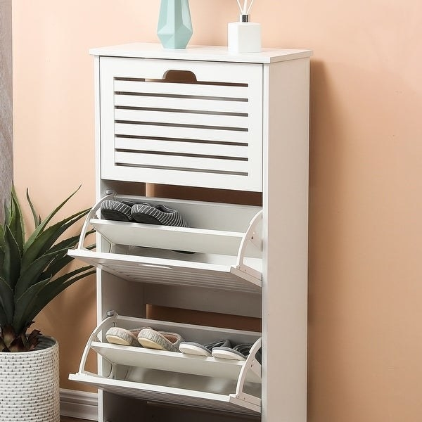 white vertical cabinet with three drawers that pivot out to reveal pairs of shoes in storage. Has vents on the drawers and a tabletop surface on top with a vase