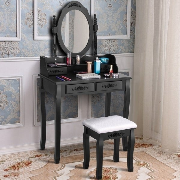 black vanity table with oval mirror, four pullout storage drawers with flower decoration handles. Comes with matching black stool with white cushion.