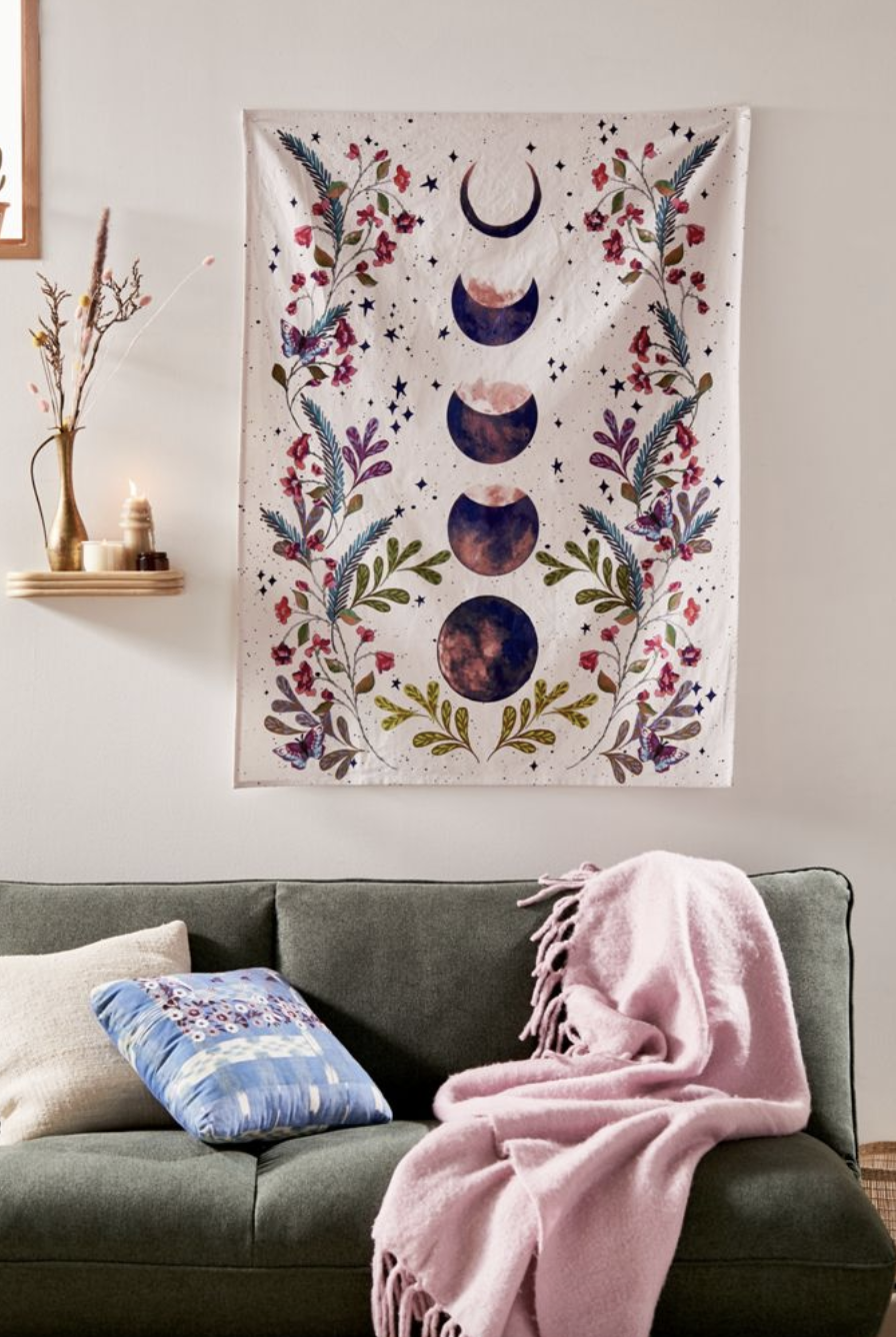 Purple and pink moon tapestry with flowers above a gray couch