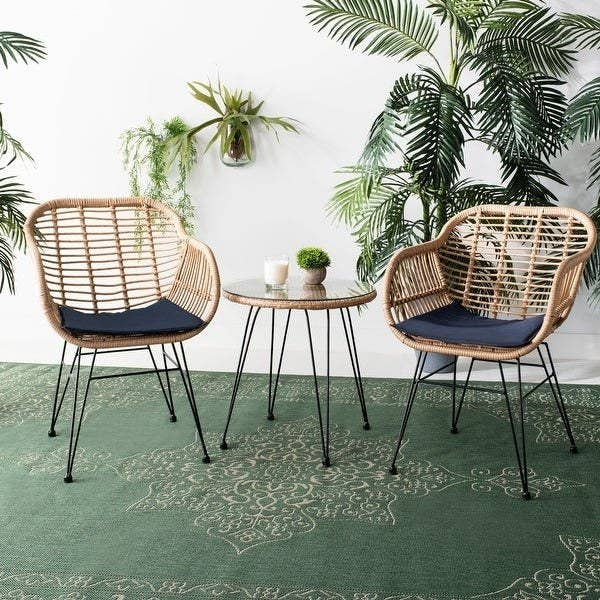 two chairs made of brown rattan with black wire legs and blue seat cushions. matching table with glass top in between the two chairs
