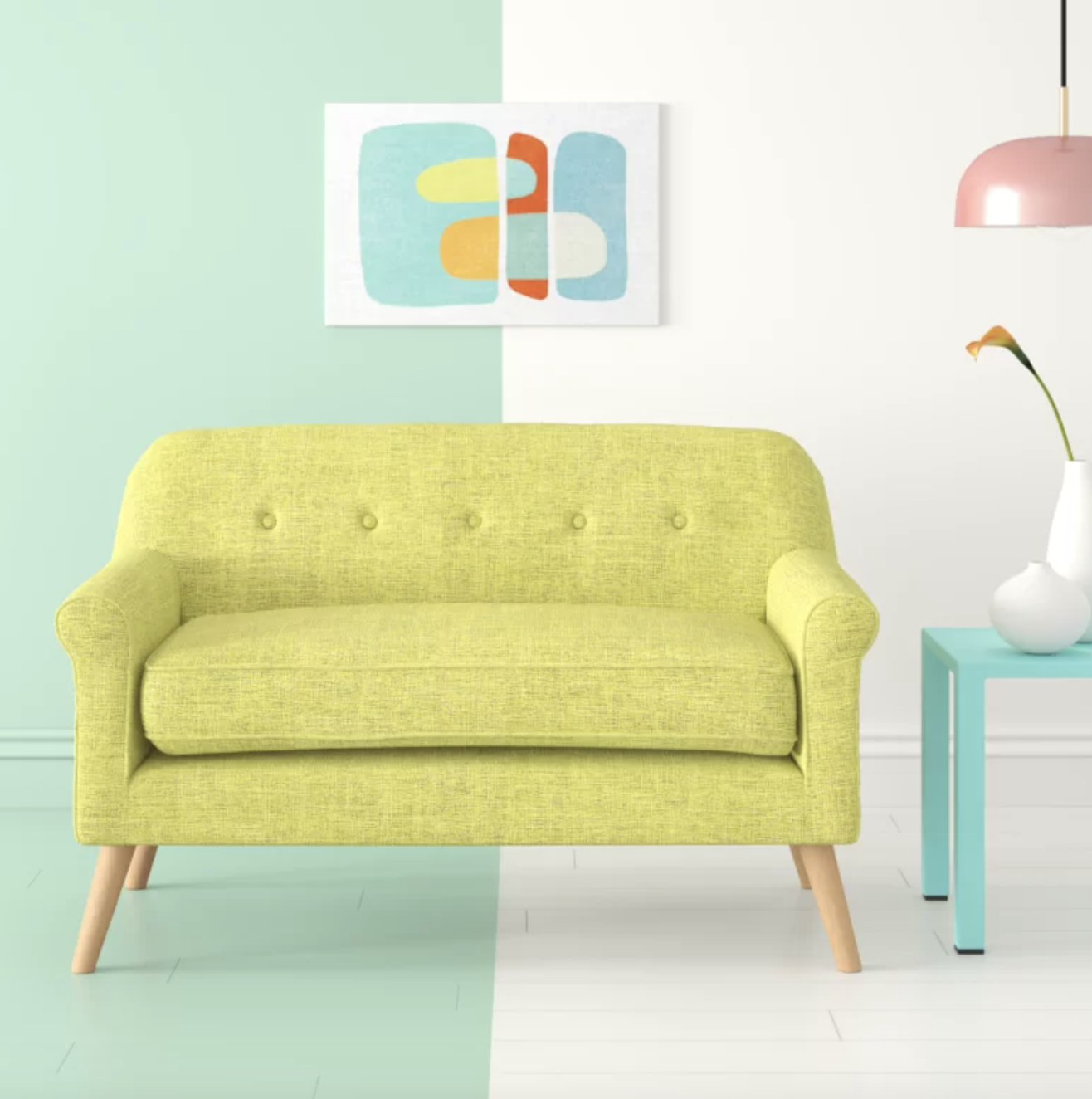 Neon yellow flared arm loveseat on a half green, half white floor next to a light blue table