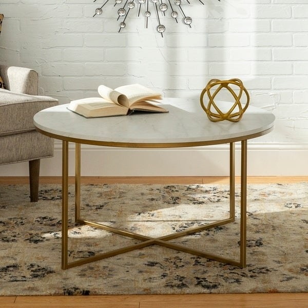 round coffee table with brass-tone legs and a white faux-marble top