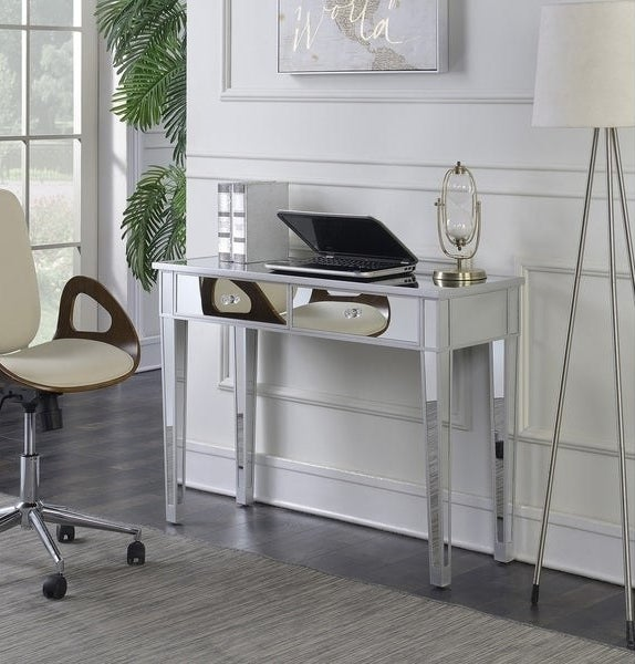 Hollywood Regency style slim mirrored desk with two front drawers. Has a laptop, lamp, and two books on top, positioned up against a wall with a desk chair nearby