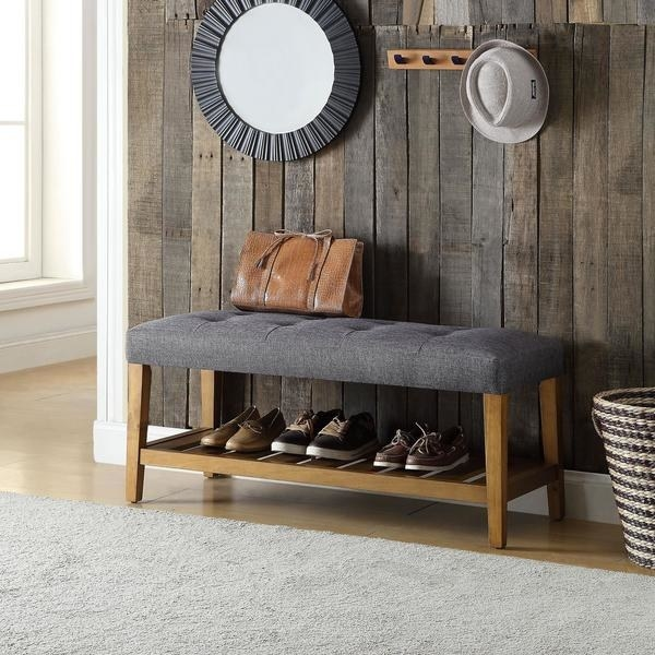 wood bench with gray tufted cushion on top and an open shelf with shoes underneath. leather bag sitting on the bench with a mirror and a strip of storage hooks on the wall behind the bench