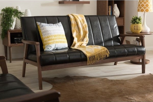 modern wood frame sofa with black faux-leather cushions with arm rests and enough room for three people to sit