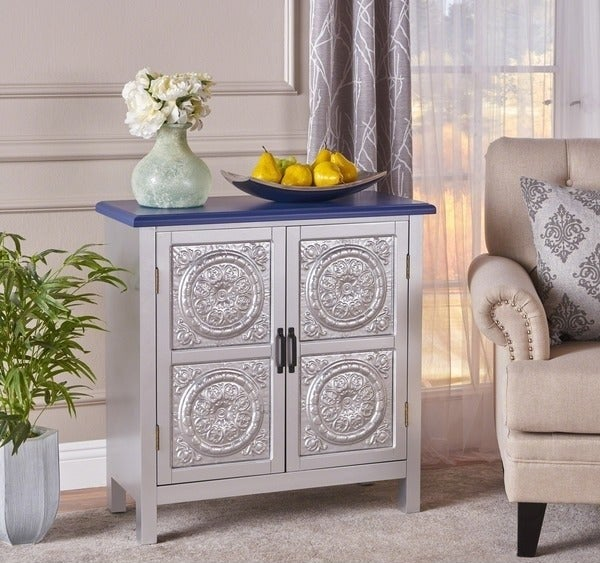 Silver farmhouse-style cabinet with two front doors, blue tabletop, black drawer pulls, and a design on the cabinet doors that look like a tin-tile ceiling