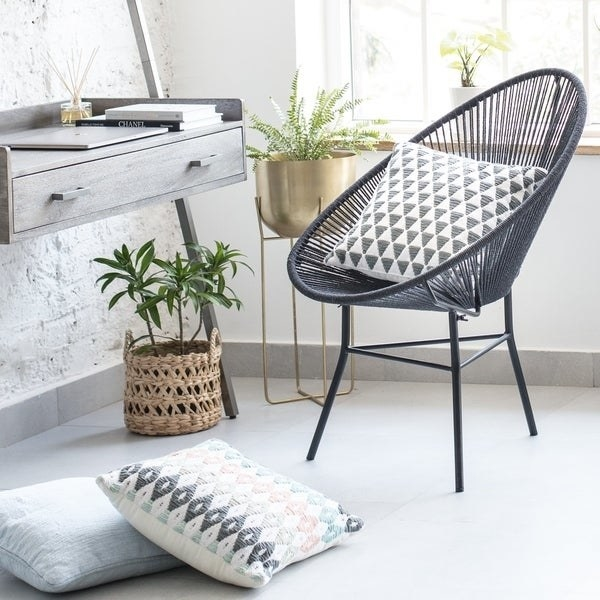 modern style dark gray chair with seat made of stretched jute rope. geometric triangle pattern pillow on chair, surrounded by plants and pillows