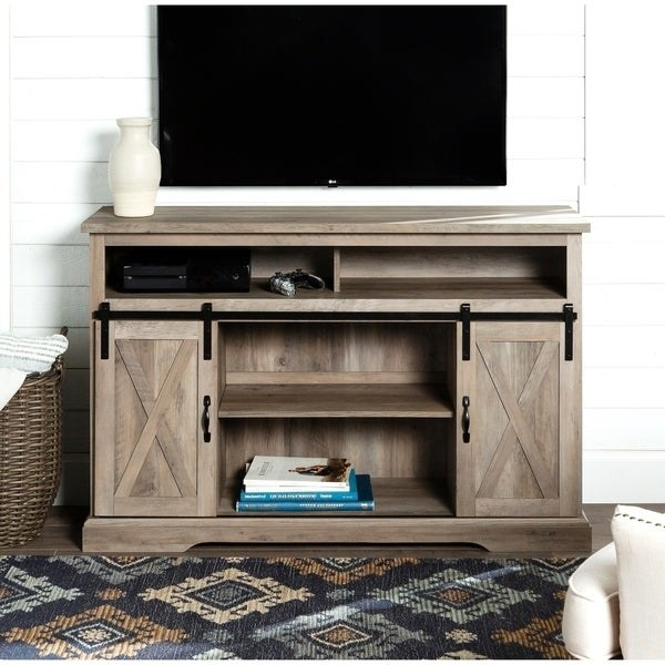 farmhouse style TV console cabinet in weathered gray wash color with TV on top, two long open shelves sized for DVD players of gaming consoles. At the bottom of the cabinet are two sliding barn-style doors with two large open storage compartments