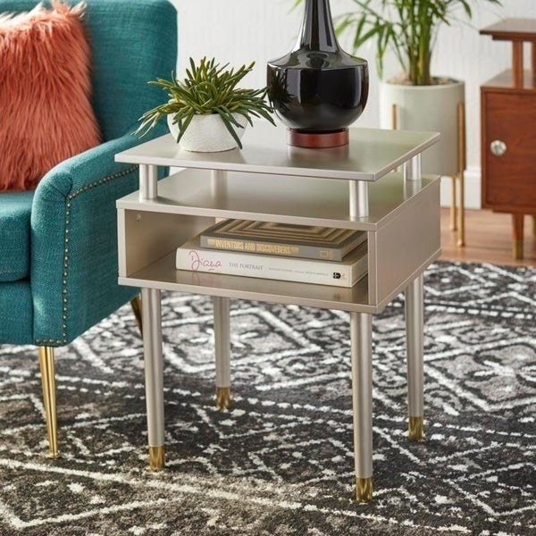 contemporary style silver tone end table with two stacked open shelves for storage. Gold tone caps for legs and height is about the arm rest of a couch