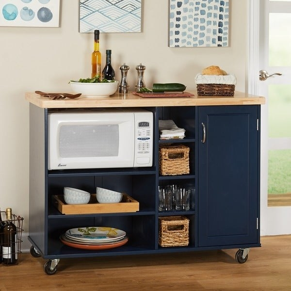 wheeled blue kitchen cart with wood butcher block top, open compartment for microwave, six more open compartments, and a cabinet door that closes.