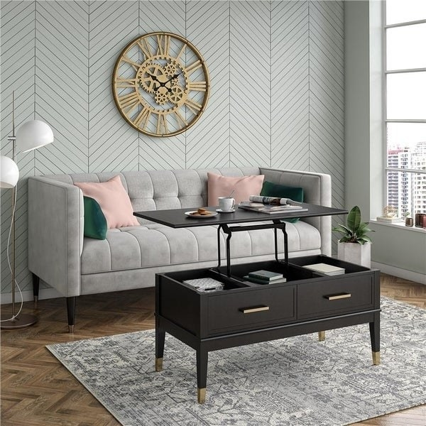 black modern coffee table with a lift top on hinges that reveals storage compartments in the coffee table for books and more
