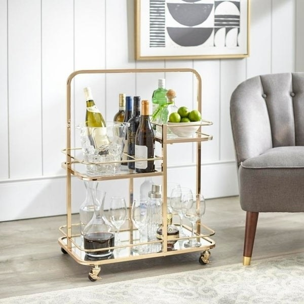 gold tone bar cart with a mirrored bottom shelf and two other staggered height shelves with glass bottoms. Rails along the shelves keep bottles and glasses in place