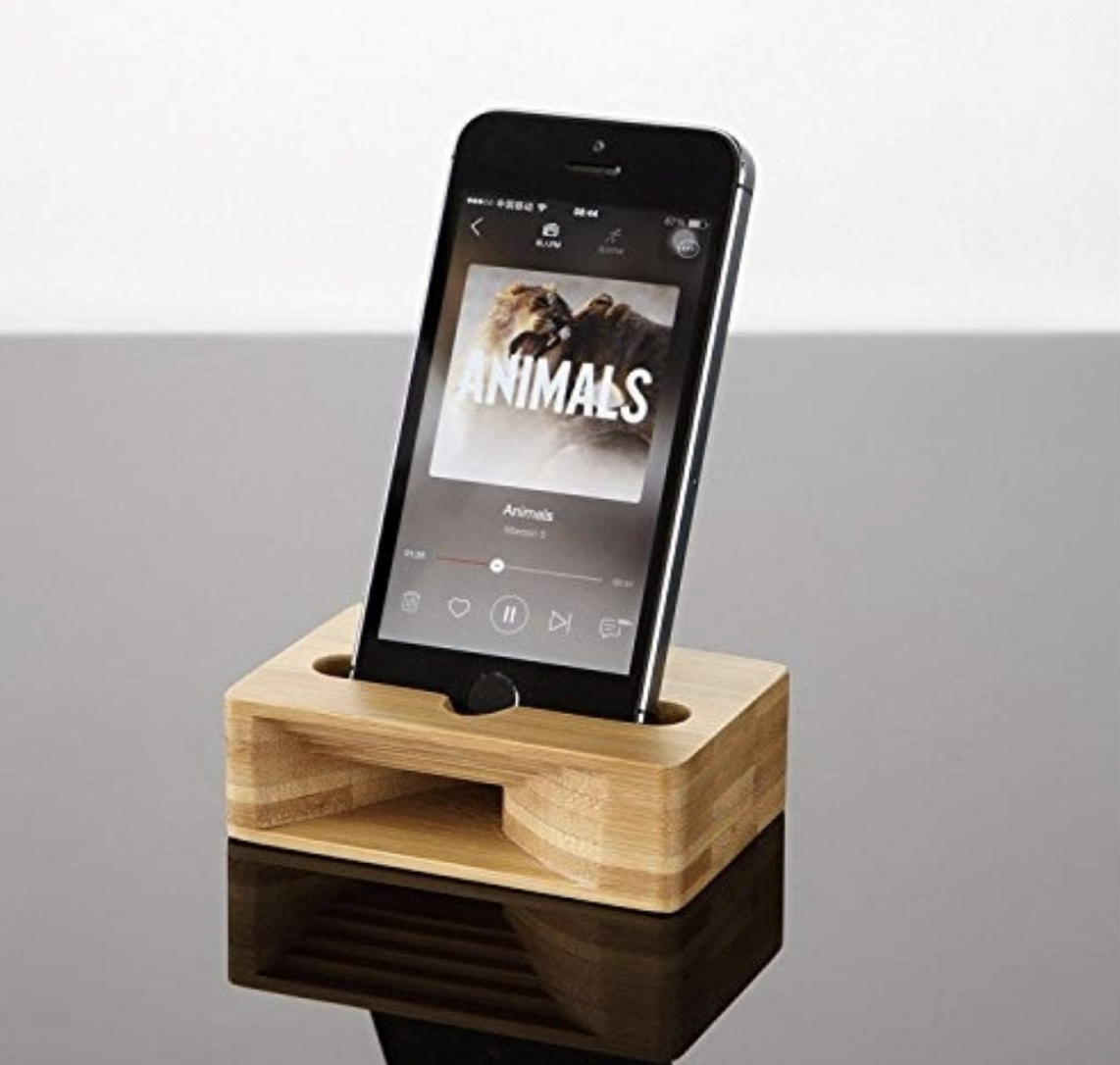 A smartphone sits in a bamboo dock.