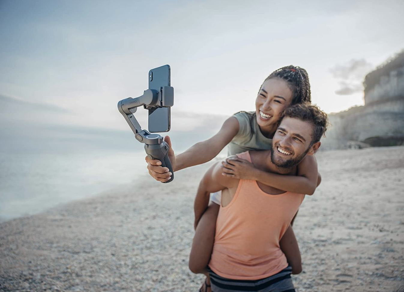 Man holding woman on back, while she films them using phone-holding device.