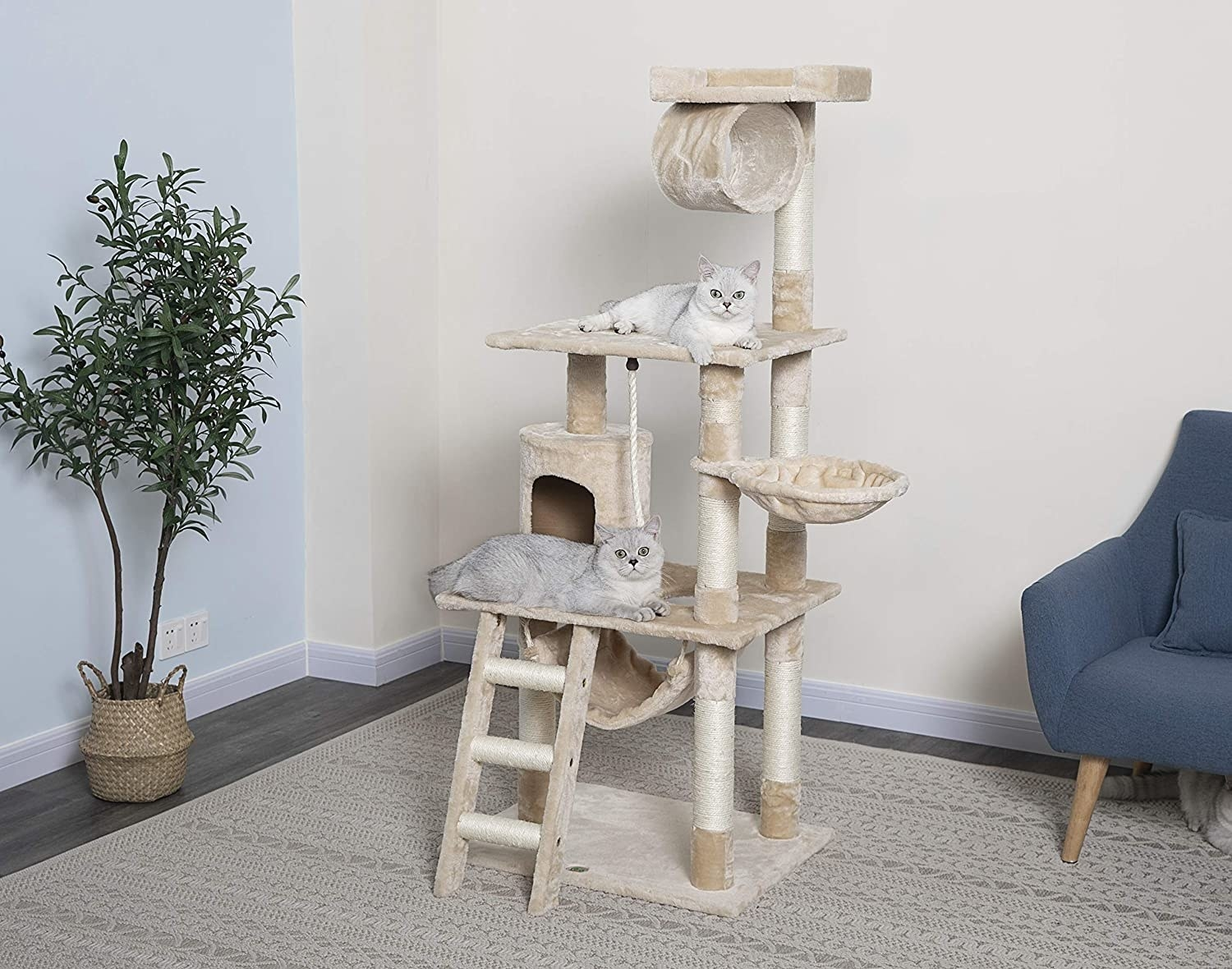 A product shot of a multi-level beige carpeted cat tower with stairs, pouches to sleep in, sisal leg posts to scratch, and nooks to explore