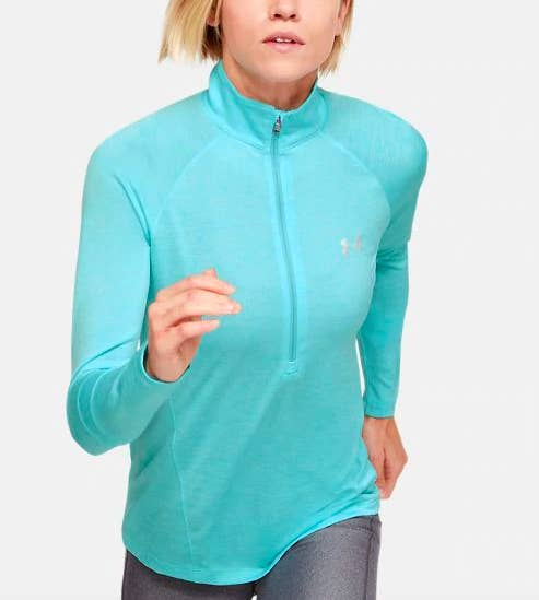 Woman running in the teal-colored version of the half-zip