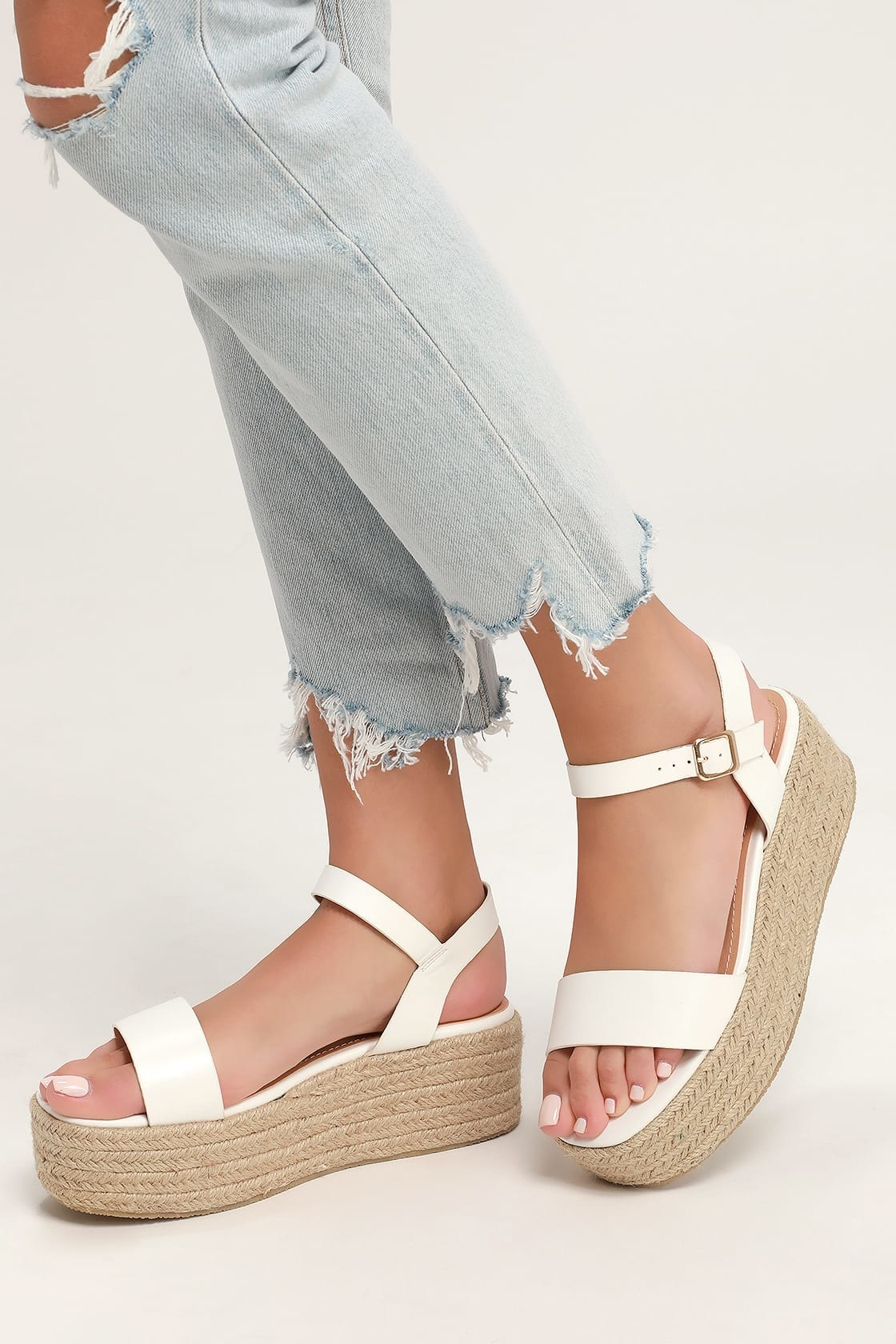 feet in strappy white platform espadrille sandals with silver buckle