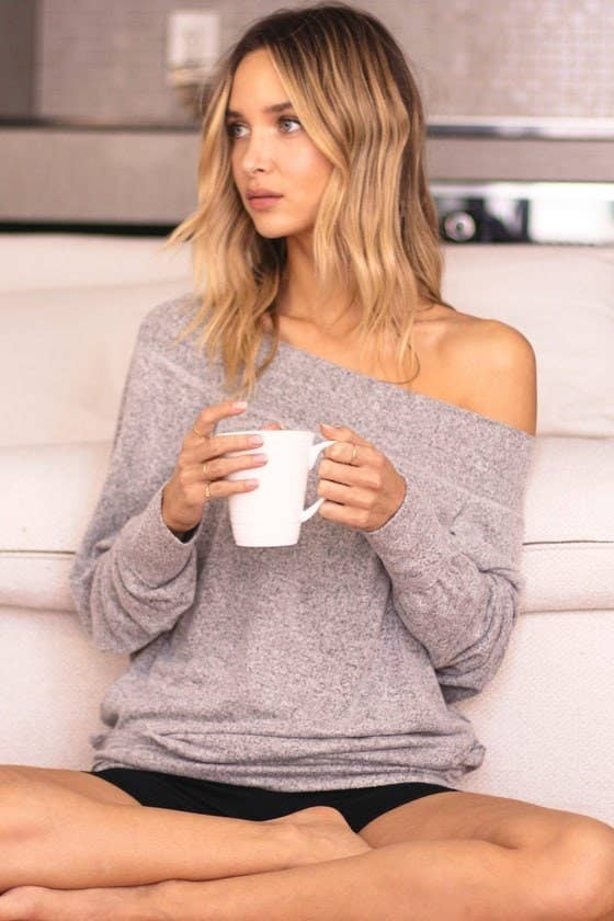 model wearing loose grey off-the-shoulder top and holding a mug