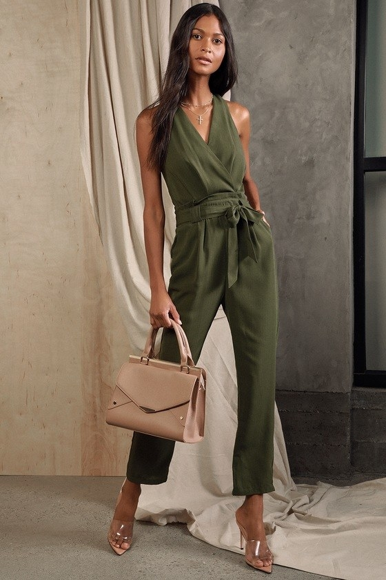 model wearing a sleeveless olive green jumpsuit with tie-waist belt and tapered legs