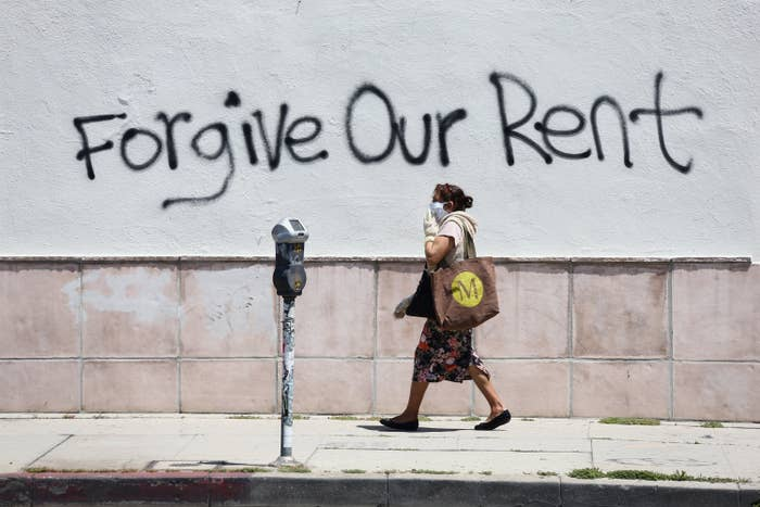"A woman wearing a mask walks past a wall with spray paint reading, ""Forgive Our Rent."""